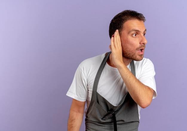 Barber man in apron holding hair cutting machine holding hand near his ear trying to listen standing over purple wall