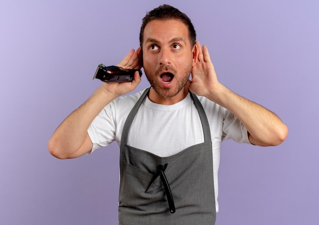Barber man in apron holding hair cutting machine holding hands near ears trying to listen looking surprised standing over purple wall