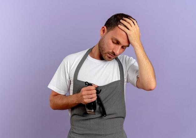 Uomo del barbiere in grembiule che tiene la macchina per tagliare i capelli che sembra confuso con la mano sulla testa per errore in piedi sul muro viola