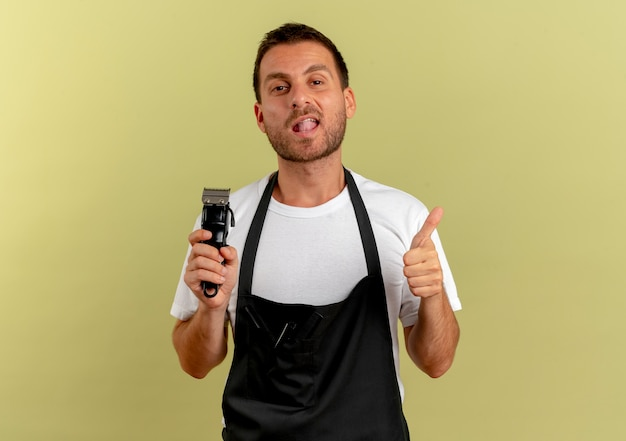 Barber man in apron holding hair cutting machine looking to the front smiling showing thumbs up standing over light wall