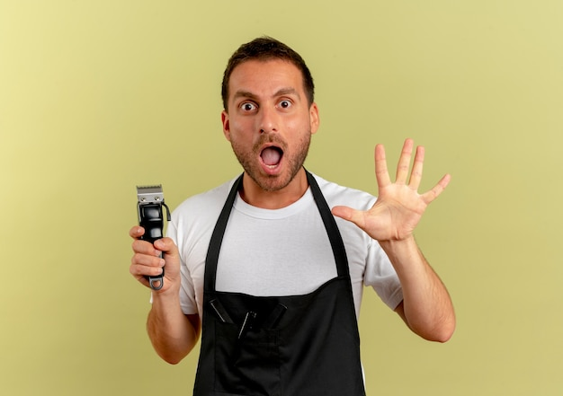 Barber man in apron holding hair cutting machine looking to the front surprised with open raised hand standing over light wall