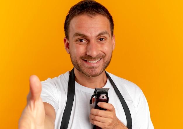 Uomo del barbiere in grembiule che tiene la macchina per tagliare i capelli guardando in avanti con il sorriso sul viso che offre la mano in piedi sopra la parete arancione