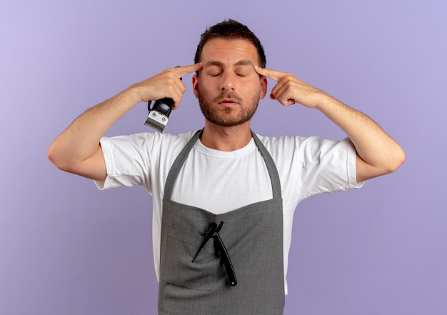 Barber man in apron holding hair cutting machine pointing his temples with closed eyes relaxing standing over purple wall