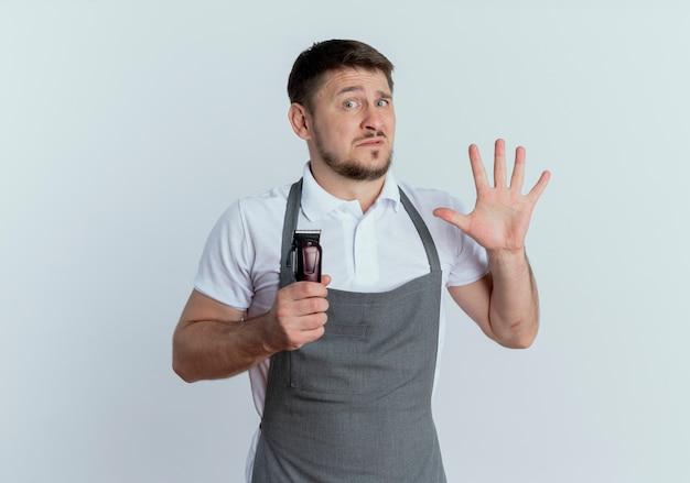 Uomo del barbiere in grembiule che tiene la macchina per il taglio dei capelli che mostra il numero cinque guardando la fotocamera atr confusa in piedi su sfondo bianco