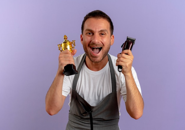 Barber man in apron holding hair cutting machine and trophy happy and excited smiling cheerfully standing over purple wall
