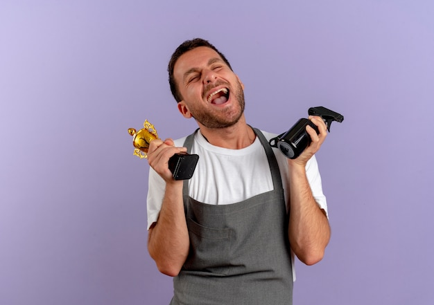 Barber man in apron holding hair cutting machine and trophy happy and excited standing over purple wall