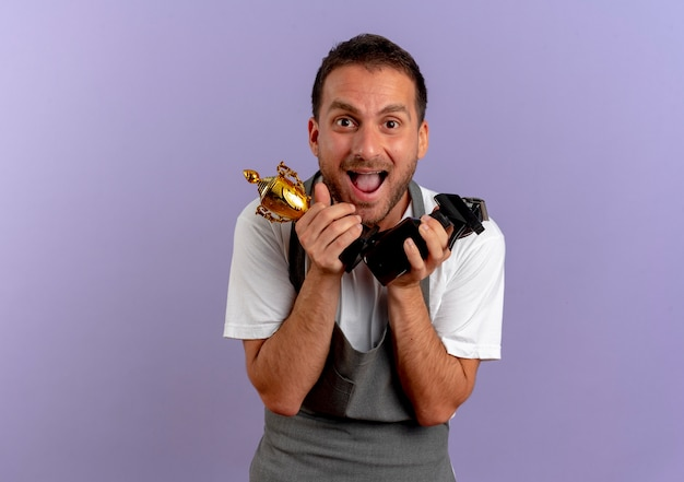 Barber man in apron holding hair cutting machine and trophy looking to the front happy and excited standing over purple wall