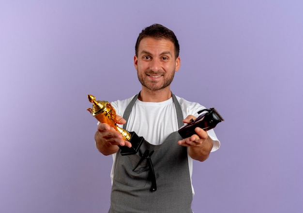 Barber man in apron holding hair cutting machine and trophy looking to the front smiling confident standing over purple wall