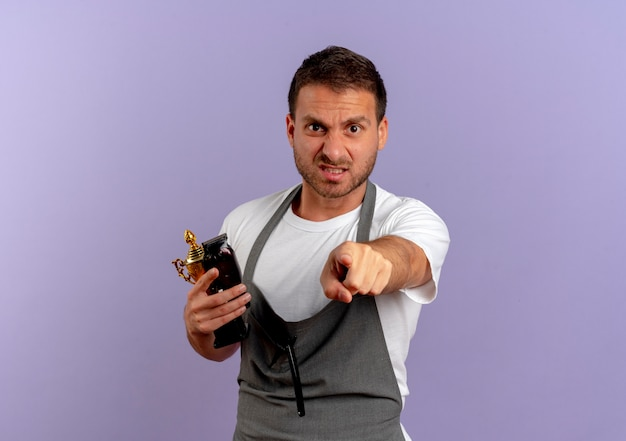 Barber man in apron holding hair cutting machine and trophy pointing with finger to the front displeased standing over purple wall
