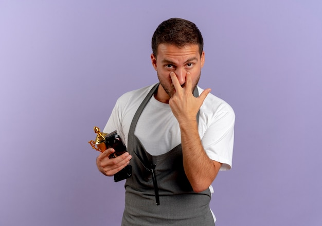 Barber man in apron holding hair cutting machine and trophy pointing with fingers to his eyes standing over purple wall