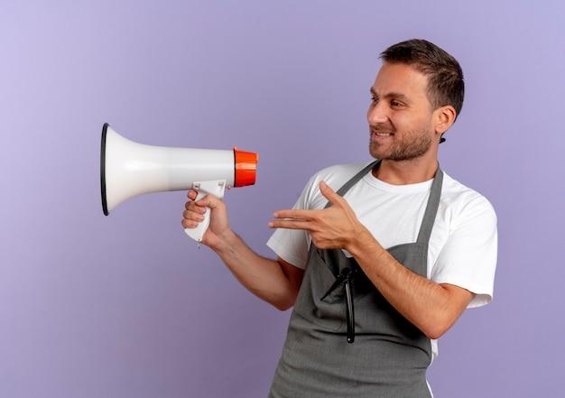 Uomo del barbiere in grembiule che tiene il megafono che osserva da parte che indica con il dito a lato in piedi sopra la parete viola