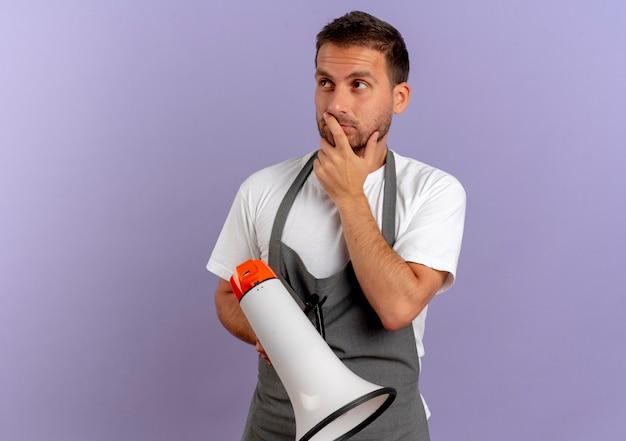 Uomo del barbiere in grembiule che tiene il megafono che osserva da parte perplesso con espressione pensierosa in piedi sopra la parete viola