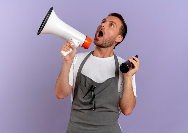 Barber man in apron holding megaphone shouting through it holding spray standing over purple wall