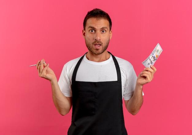 Uomo del barbiere in grembiule che tiene forbici e contanti guardando in avanti confuso e molto ansioso in piedi sopra il muro rosa