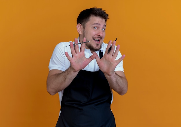 Barber man in apron holding scissors and comb making stop gesture with hands standing over orange background