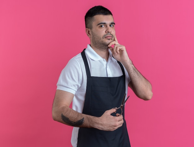 Uomo del barbiere in grembiule che tiene le forbici guardando la telecamera perplesso in piedi su sfondo rosa