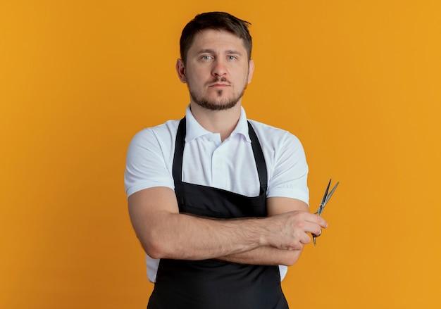 Barbiere uomo in grembiule tenendo le forbici guardando la fotocamera con seria espressione fiduciosa in piedi su sfondo arancione
