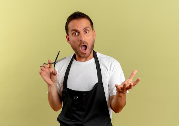 Uomo del barbiere in grembiule che tiene le forbici guardando in avanti stupito e sorpreso in piedi sopra la parete chiara