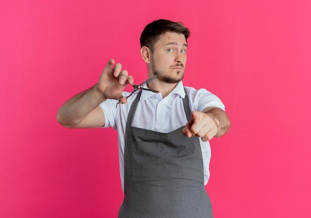 Uomo del barbiere in grembiule tenendo le forbici rivolte con l'indice alla fotocamera con espressione fiduciosa in piedi su sfondo rosa