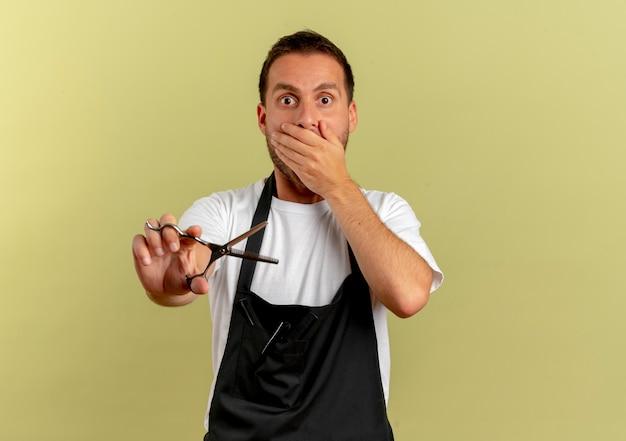 Uomo del barbiere in grembiule che tiene le forbici scioccato che copre la bocca con la mano in piedi sopra la parete leggera