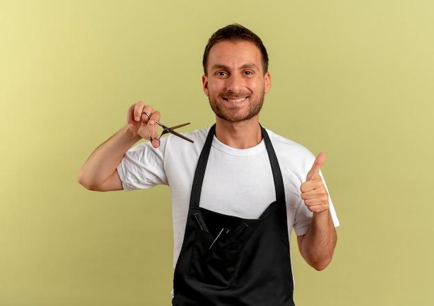 Uomo del barbiere in grembiule che tiene le forbici sorridente che mostra i pollici in su in piedi sopra la parete chiara