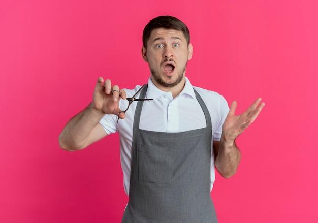 Uomo del barbiere in grembiule che tiene le forbici sorpreso e stupito con il braccio alzato in piedi su sfondo rosa