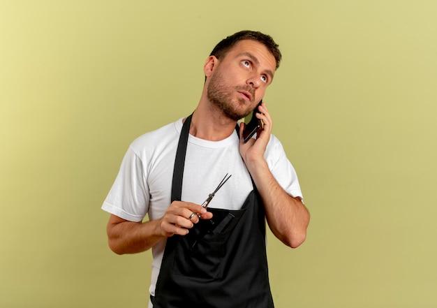 Uomo del barbiere in grembiule che tiene le forbici parlando al cellulare con la faccia seria in piedi sopra la parete chiara