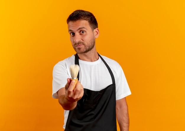 Uomo del barbiere in grembiule tenendo il pennello da barba guardando in avanti con espressione fiduciosa in piedi sopra la parete arancione