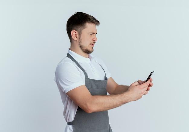 Uomo del barbiere in grembiule tenendo lo smartphone guardando lo schermo con la faccia seria in piedi su sfondo bianco