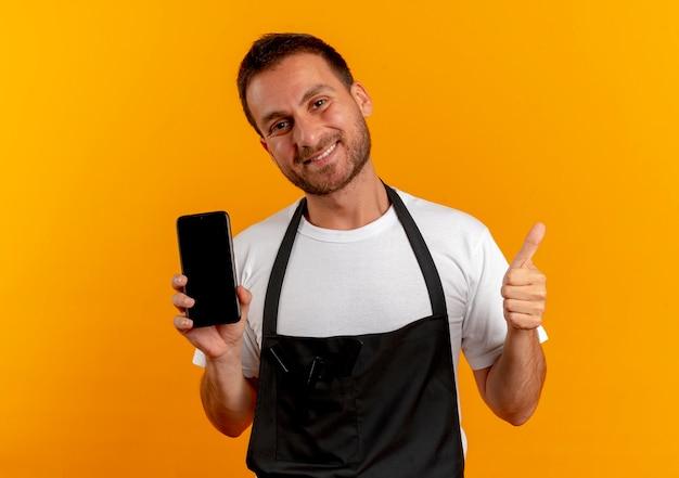 Uomo del barbiere in grembiule che tiene smartphone sorridendo allegramente mostrando i pollici in su guardando in avanti in piedi sopra la parete arancione