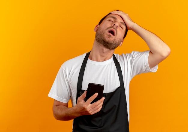 Uomo del barbiere in grembiule che tiene smartphone con la mano sulla sua testa che sembra infastidito e sovraccarico di lavoro in piedi sopra la parete arancione