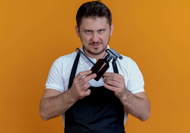 Barber man in apron holding spray and comb  with serious face crossing hands standing over orange wall