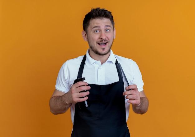 Barbiere uomo in grembiule azienda spray e forbici guardando la telecamera sorridente con la faccia felice in piedi su sfondo arancione