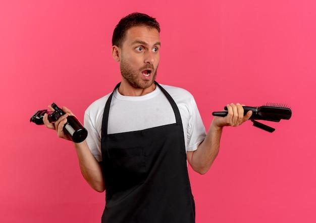 Uomo del barbiere in grembiule che tiene spray con spazzola per capelli d'acqua e trimmer guardando da parte confuso in piedi sopra il muro rosa