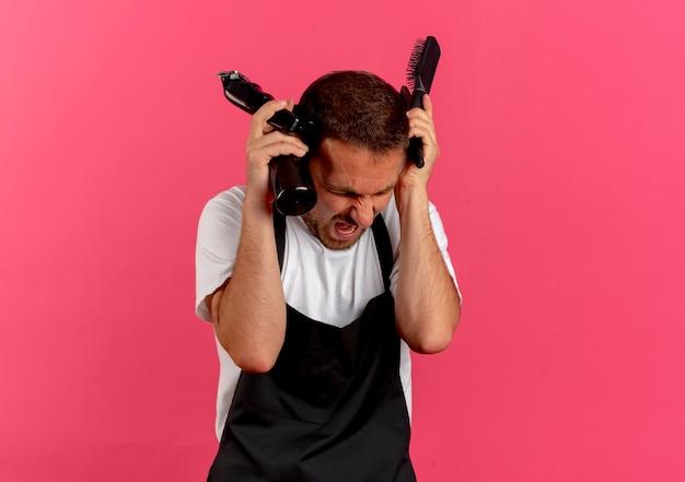 Uomo del barbiere in grembiule che tiene spray con spazzola per capelli d'acqua e trimmer gridando con espressione aggressiva in piedi sopra il muro rosa