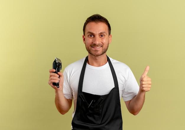 Uomo del barbiere in grembiule che tiene trimmer sorridendo allegramente mostrando i pollici in piedi sopra la parete leggera