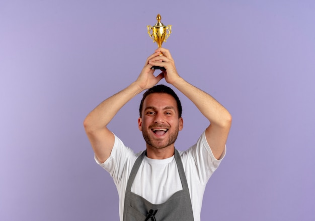 Barber man in apron holding trophy over his head happy and excited standing over purple wall