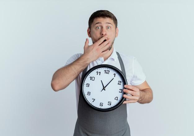 Barbiere uomo in grembiule tenendo l'orologio da parete che copre la bocca con la mano scioccata in piedi sul muro bianco