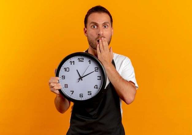 Uomo del barbiere in grembiule che tiene orologio da parete che sembra sorpreso e stupito che copre la bocca con la mano in piedi sul muro arancione
