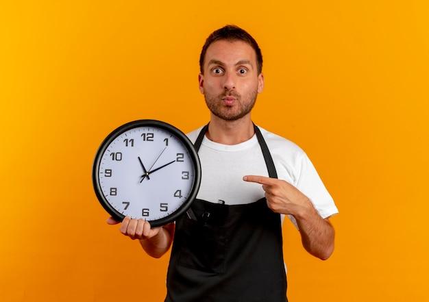 Uomo del barbiere in grembiule che tiene l'orologio da parete che indica con il dito che sembra sorpreso in piedi sopra la parete arancione
