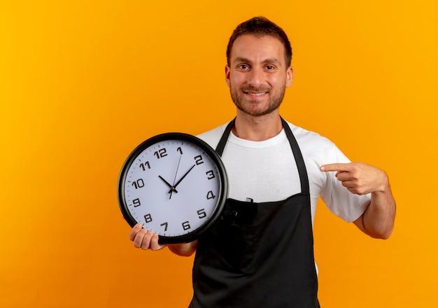 Uomo del barbiere in grembiule che tiene l'orologio da parete che punta con il dito ad esso sorridente fiducioso in piedi sopra la parete arancione