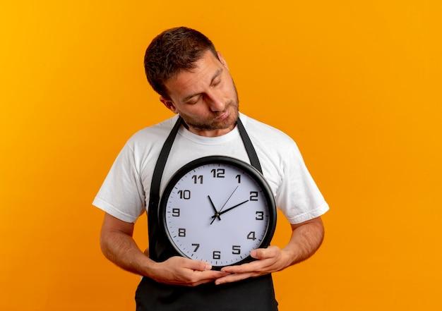 Uomo del barbiere in grembiule che tiene orologio da parete con gli occhi chiusi sensazione di emozioni grate e positive in piedi sopra la parete arancione