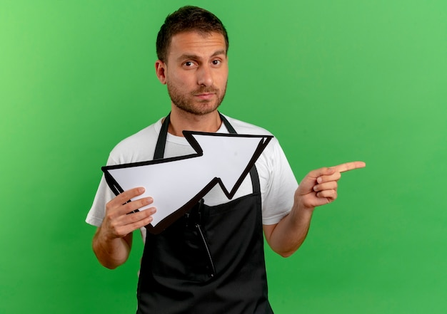 Barber man in apron holding white arrow looking to the front with serious face pointing with index finger to the side standing over green wall