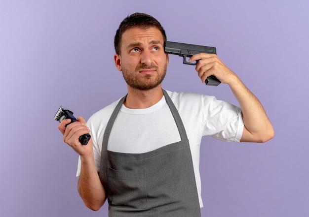 Uomo del barbiere in grembiule che tiene la pistola vicino al suo tempio che sembra scontento in piedi sopra il muro blu
