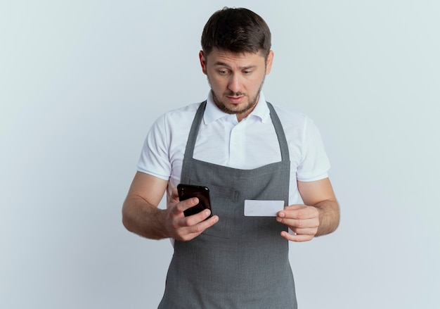 Barbiere uomo in grembiule loking confuso tenendo lo smartphone e la carta di credito in piedi su sfondo bianco