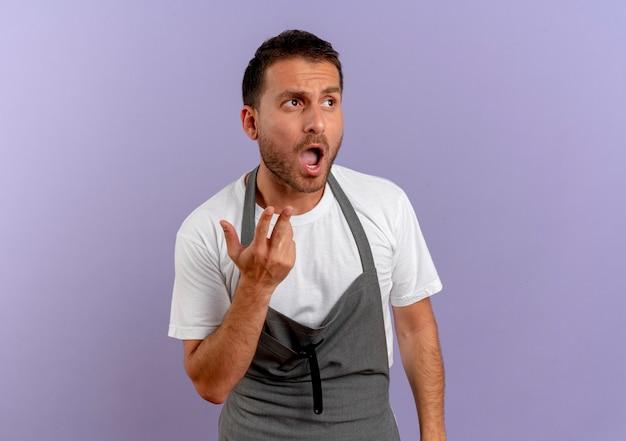 Uomo del barbiere in grembiule che osserva da parte confuso con il braccio fuori come chiedere o discutere in piedi sul muro viola