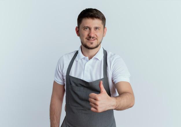 Uomo del barbiere in grembiule che guarda l'obbiettivo sorridente fiducioso che mostra i pollici in su in piedi su sfondo bianco