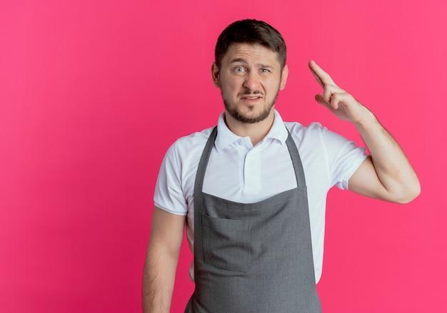 Uomo del barbiere in grembiule che guarda l'obbiettivo con sorriso scettico alzando il braccio in piedi su sfondo rosa
