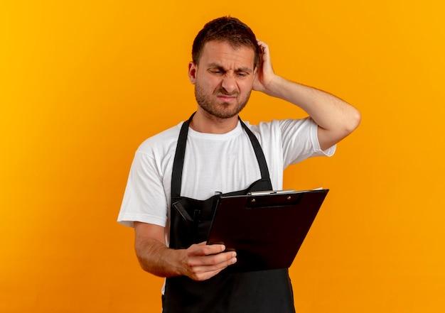 Uomo del barbiere in grembiule guardando appunti con espressione confusa in piedi sopra la parete arancione