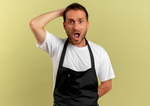 Uomo del barbiere in grembiule che guarda in avanti confuso e molto ansioso con la mano sulla testa in piedi sopra il muro leggero